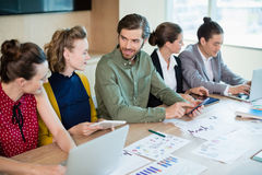 Smiling business team interacting with each other in conference room Stock Images