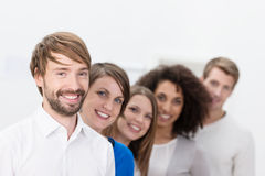 Smiling business team leader with his team. Smiling young male business team leader with his successful young multiethnic team grouped behind him in a line Stock Image