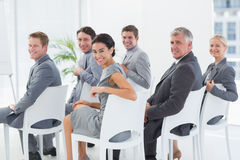 Smiling business team looking at camera during conference Stock Images