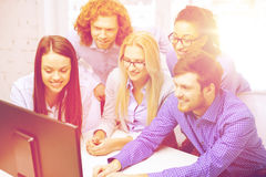 Smiling business team looking at computer monitor Stock Images
