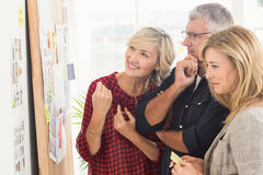 Smiling business team looking at notes on the wall Royalty Free Stock Photography