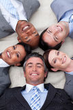 Smiling business team lying on the floor Royalty Free Stock Images