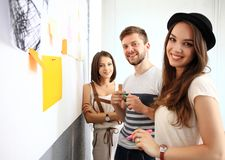 Smiling business team with marker and stickers working. Business, people, teamwork and planning concept - smiling business team with marker and stickers working royalty free stock image
