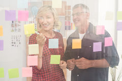 Smiling business team pointing post its on the wall Stock Photos