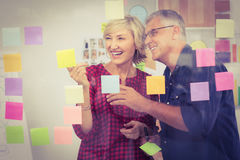 Smiling business team pointing post its on the wall Stock Photography