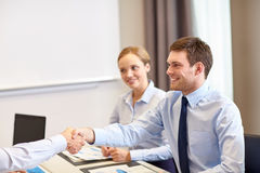 Smiling business team shaking hands in office Stock Photography