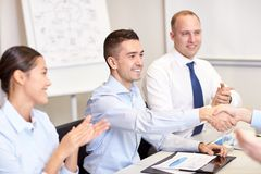 Smiling business team shaking hands in office Stock Photo