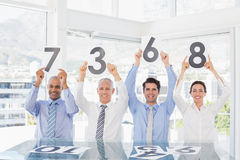 Smiling business team showing paper with rating Royalty Free Stock Photo