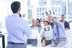 Smiling business team showing paper with rating Stock Image
