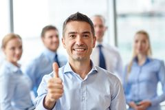 Smiling business team showing thumbs up in office Royalty Free Stock Photos
