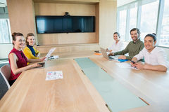 Smiling business team sitting in conference room Stock Photos