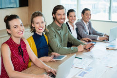 Smiling business team sitting in conference room Stock Photo