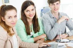 Smiling business team. Sitting at the desk Stock Images