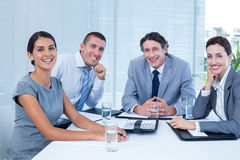 Smiling business team sitting at desk Stock Photos