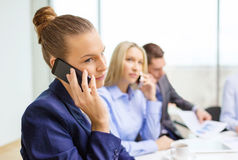 Smiling business team with smartphones in office Royalty Free Stock Images