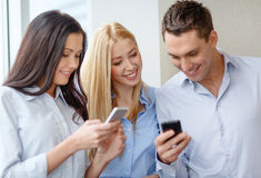 Smiling business team with smartphones in office Stock Photography