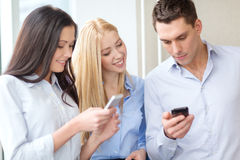 Smiling business team with smartphones in office Royalty Free Stock Image
