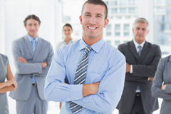 Smiling business team standing with arms crossed Stock Images