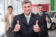 Smiling business team standing while giving thumbs up Royalty Free Stock Photography