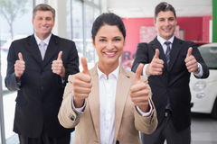 Smiling business team standing while giving thumbs up Stock Images