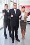 Smiling business team standing while giving thumbs up Royalty Free Stock Photo