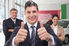 Smiling business team standing while one giving thumbs up Royalty Free Stock Photography