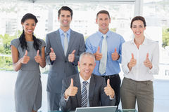 Smiling business team standing thumbs up Royalty Free Stock Photography