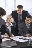 Smiling business team talking in office. Happy business people talking over documents in office smiling Royalty Free Stock Images