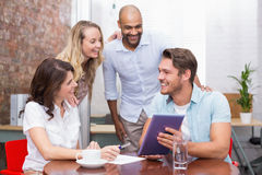 Smiling business team watching a tablet computer Stock Photos