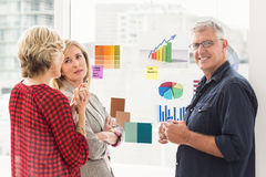 Smiling business team working on flow charts. Portrait of a business team working on flow charts at the office royalty free stock images