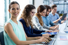 Smiling business team working on laptop and digital tablet in meeting Stock Photos