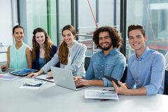 Smiling business team working on laptop and digital tablet in meeting Royalty Free Stock Image