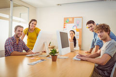 Smiling business team working on laptops Royalty Free Stock Images