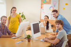 Smiling business team working on laptops. Portrait of smiling business team working on laptops in a bright office Stock Photography