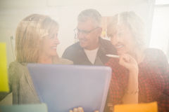 Smiling business team working over a tablet Royalty Free Stock Photo