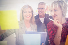 Smiling business team working on tablet Stock Images