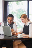 Smiling business team working together in a cafe. With laptop Royalty Free Stock Photo