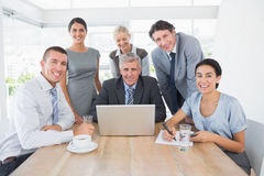 Smiling business team working together on laptop Stock Photo