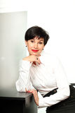 Smiling business woman. Business Woman sitting near the table (Smiling royalty free stock photography
