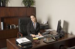 Smiling business woman. Young business woman in mahogany office Royalty Free Stock Photo