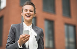 Smiling business woman against office building writing sms Stock Photography