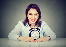 Smiling business woman with alarm clock sitting at table stock photography