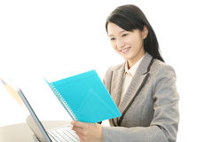 Smiling business woman. Asian business woman sitting at desk working on laptop Stock Photos