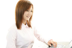 Smiling business woman. Asian business woman sitting at desk working on laptop Stock Image