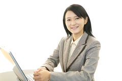 Smiling business woman. Asian business woman sitting at desk working on laptop Stock Photography