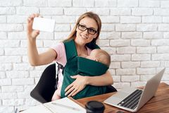 Smiling business woman with baby making selfie. stock images