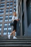 Smiling business woman with bag and cell phone against office building stock images