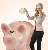 Smiling business woman with big coin in piggy bank Royalty Free Stock Photos