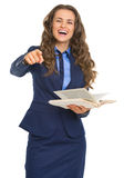Smiling business woman with book pointing in camera Stock Images