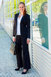 Smiling business woman with briefcase at office Stock Images